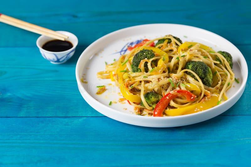 Τρόφιμα της Ασίας Ανακατώστε τα νουντλς τηγανητών με τα λαχανικά σε ένα μπλε ξύλινο backgound, που μαγειρεύεται στο wok στοκ φωτογραφία