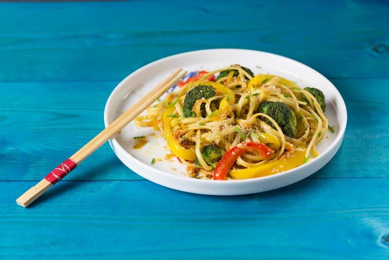 Τρόφιμα της Ασίας Ανακατώστε τα νουντλς τηγανητών udon με τα λαχανικά σε ένα άσπρο πιάτο, μπλε ξύλινο backgound, που μαγειρεύεται στοκ φωτογραφίες