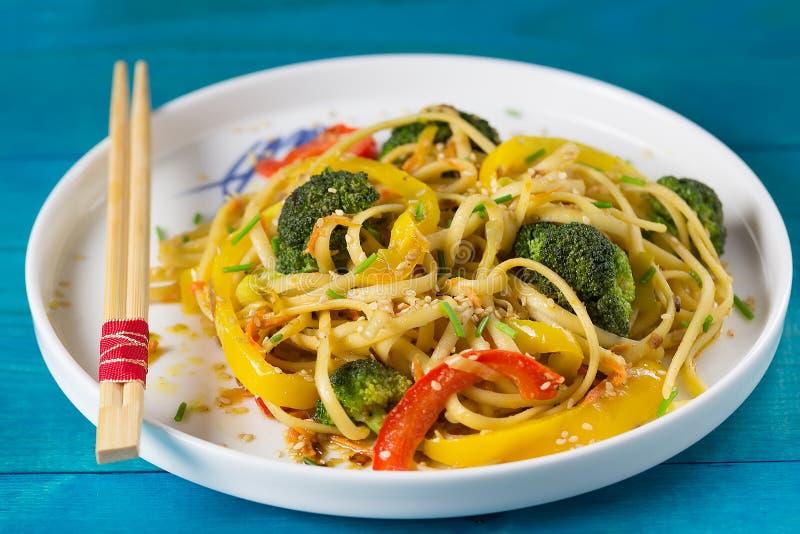 Τρόφιμα της Ασίας Ανακατώστε τα νουντλς τηγανητών udon με τα λαχανικά σε ένα μπλε ξύλινο backgound, που μαγειρεύεται στο wok στοκ εικόνα με δικαίωμα ελεύθερης χρήσης