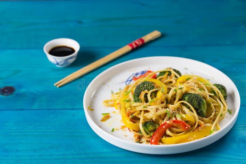 Τρόφιμα της Ασίας Ανακατώστε τα νουντλς τηγανητών udon με τα λαχανικά σε ένα άσπρο πιάτο, μπλε ξύλινο backgound, που μαγειρεύεται στοκ εικόνα