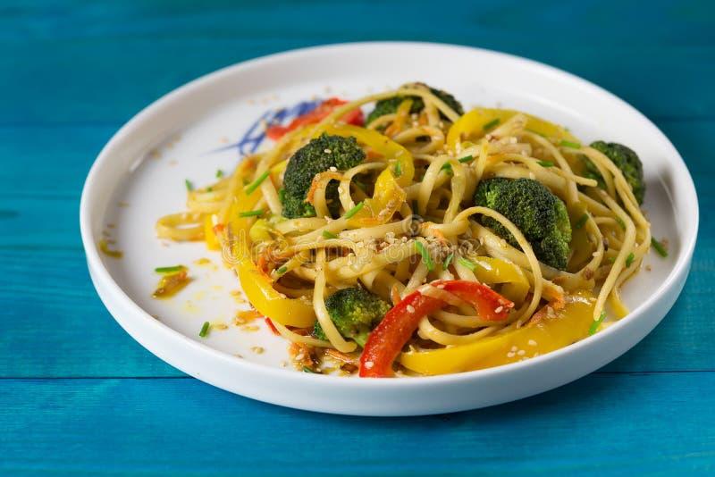 Τρόφιμα της Ασίας Ανακατώστε τα νουντλς τηγανητών udon με τα λαχανικά σε ένα μπλε ξύλινο backgound, που μαγειρεύεται στο wok στοκ εικόνες