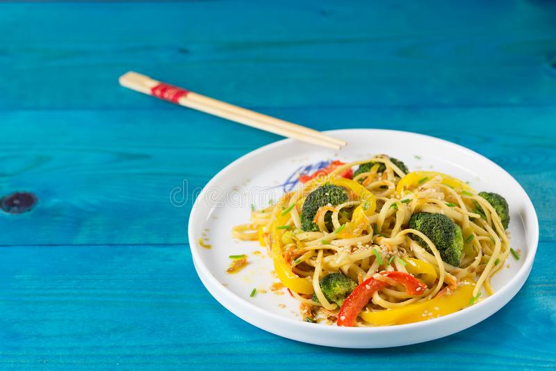 Τρόφιμα της Ασίας Ανακατώστε τα νουντλς τηγανητών udon με τα λαχανικά σε ένα άσπρο πιάτο, μπλε ξύλινο backgound, που μαγειρεύεται στοκ φωτογραφία