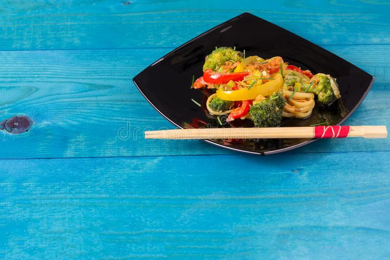 Τρόφιμα της Ασίας Ανακατώστε τα νουντλς τηγανητών udon με τα λαχανικά σε ένα μαύρο πιάτο, μπλε ξύλινο backgound, που μαγειρεύεται στοκ εικόνες με δικαίωμα ελεύθερης χρήσης