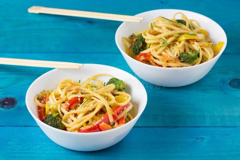 Τρόφιμα της Ασίας Ανακατώστε τα νουντλς τηγανητών udon με τα λαχανικά στα κύπελλα, μπλε ξύλινο backgound, που μαγειρεύεται στο wo στοκ φωτογραφία με δικαίωμα ελεύθερης χρήσης