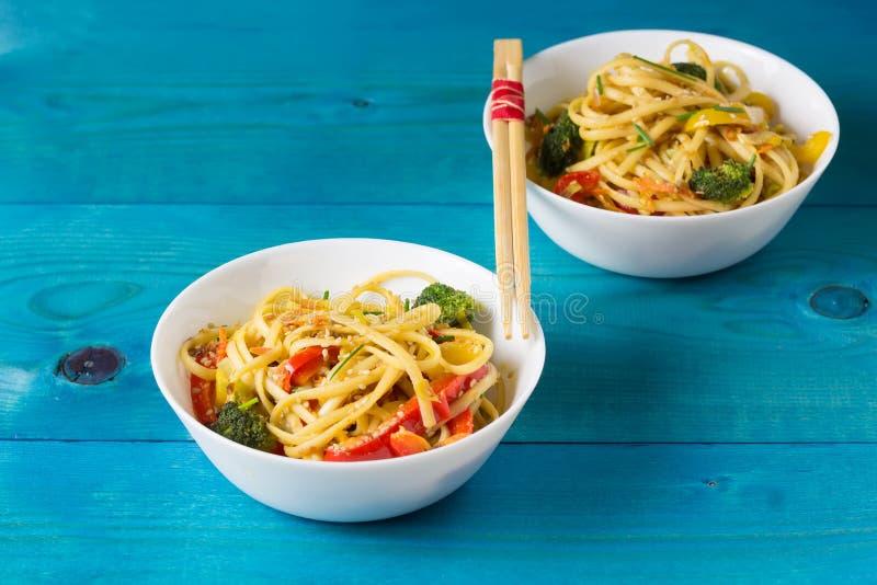 Τρόφιμα της Ασίας Ανακατώστε τα νουντλς τηγανητών udon με τα λαχανικά στα κύπελλα σε ένα μπλε ξύλινο backgound, που μαγειρεύεται  στοκ εικόνα