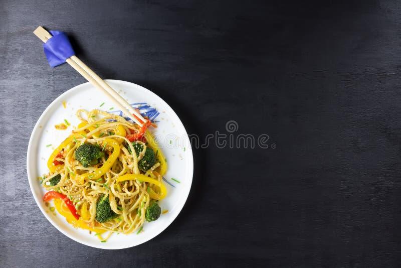 Τρόφιμα της Ασίας Ανακατώστε τα νουντλς τηγανητών udon με τα λαχανικά στο μαύρο πίνακα, που μαγειρεύεται στο wok με τη διαστημική στοκ φωτογραφία με δικαίωμα ελεύθερης χρήσης