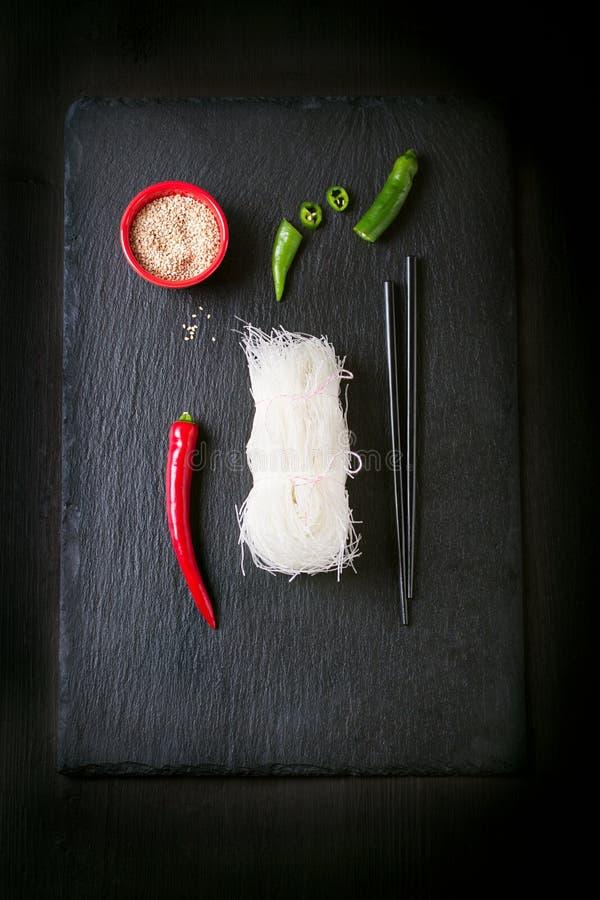 Τρόφιμα της Ασίας - νουντλς ρυζιού, πικάντικο πιπέρι, ραβδιά και sesam, έτοιμο να μαγειρεψει σε ένα σκοτεινό υπόβαθρο πετρών στοκ φωτογραφία με δικαίωμα ελεύθερης χρήσης