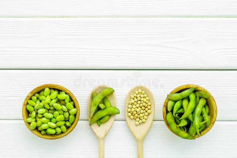 Τρόφιμα Vegan με την πράσινη σόγια ή edamame στο κουτάλι και κύπελλο στο άσπρο ξύλινο διάστημα αντιγράφων άποψης υποβάθρου τοπ στοκ εικόνα με δικαίωμα ελεύθερης χρήσης