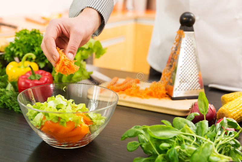 Τρόφιμα Vegan - που προετοιμάζουν τη φυτική σαλάτα με τα ξυμένα καρότα στοκ εικόνα με δικαίωμα ελεύθερης χρήσης