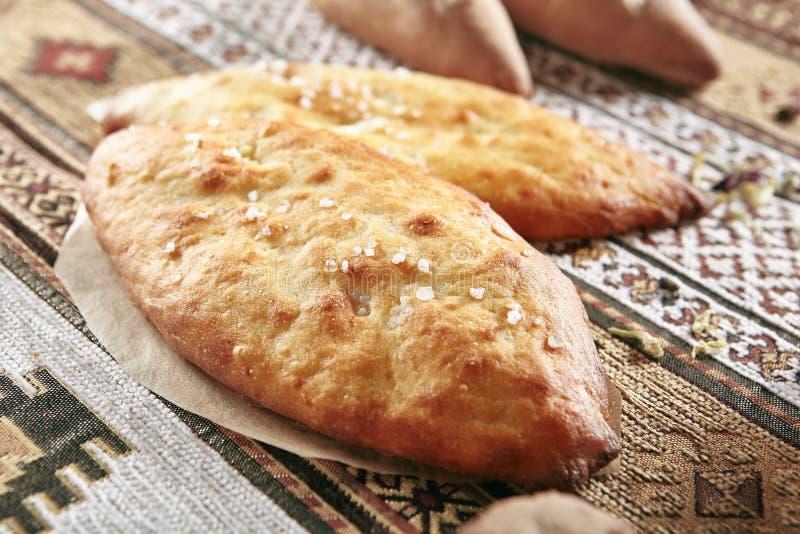 Τρύγος που εξυπηρετεί το σπιτικό ψωμί Lepeshka με το άλας στο παραδοσιακό αγροτικό τραπεζομάντιλο στοκ φωτογραφία