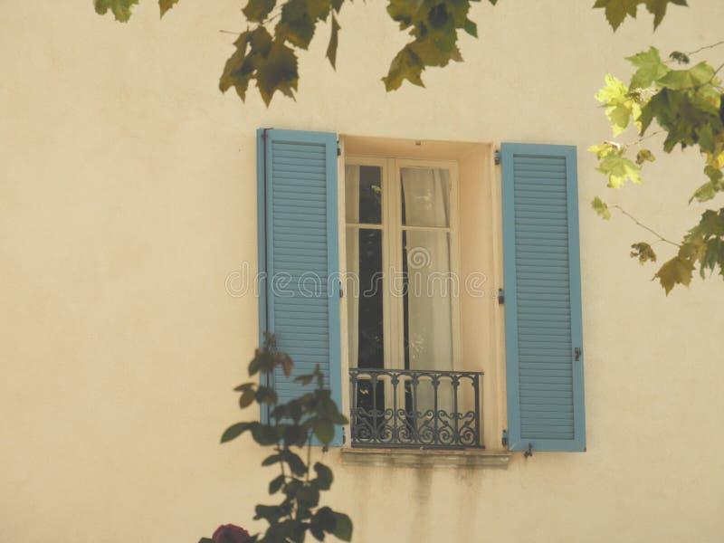 Τρύγος που φαίνεται γαλλικό παράθυρο με τα κυανά μπλε παραθυρόφυλλα στοκ φωτογραφίες