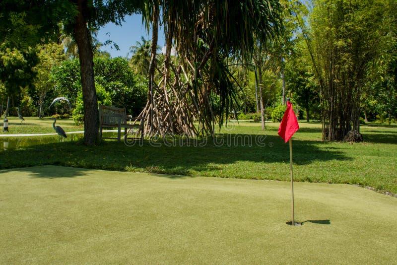 Τρύπα που μαρκάρεται με τη κόκκινη σημαία στη μίνι περιοχή γκολφ στοκ εικόνες με δικαίωμα ελεύθερης χρήσης