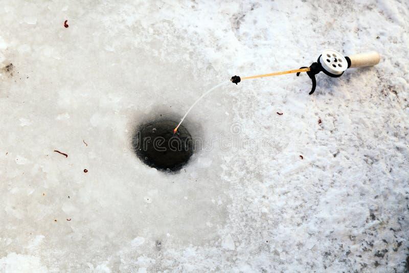 Τρύπα στον πάγο για τη χειμερινή αλιεία και μια ράβδος αλιείας με μια γραμμή εξελίκτρων και αλιείας και το δόλωμα Έννοια για το α στοκ φωτογραφία