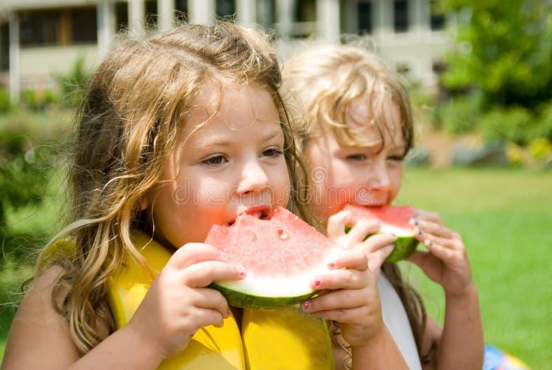 τρώγοντας τα κορίτσια δύο καρπούζι στοκ φωτογραφία