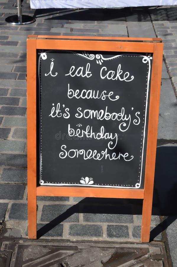Τρώω το σημάδι επιλογών κέικ στο πεζοδρόμιο στοκ φωτογραφίες
