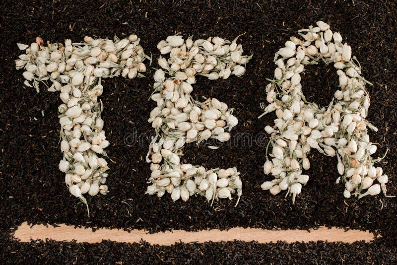 Τσάι λέξης φιαγμένο από ξηρούς jasmine οφθαλμούς λουλουδιών πέρα από τα μαύρα φύλλα τσαγιού στοκ εικόνα με δικαίωμα ελεύθερης χρήσης
