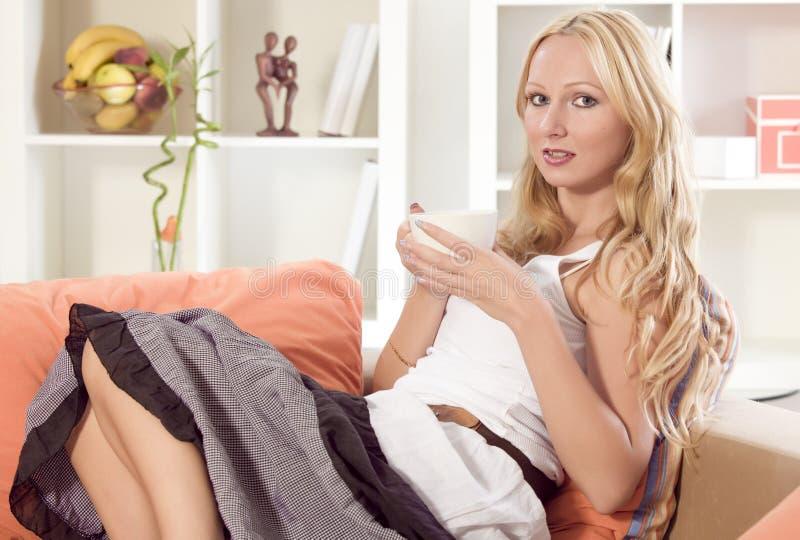 Τσάι κατανάλωσης γυναικών στον καναπέ στοκ εικόνα