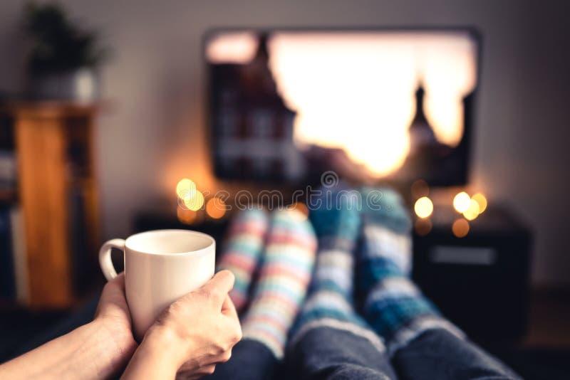 Τσάι κατανάλωσης ζεύγους, καυτή σοκολάτα, eggnog ή θερμαμένες κρασί και TV προσοχής στις θερμές άνετες μάλλινες κάλτσες το χειμών στοκ εικόνα