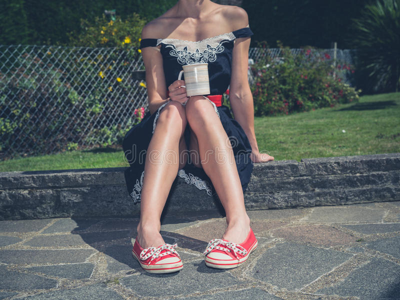 Τσάι κατανάλωσης γυναικών στον κήπο στοκ εικόνες