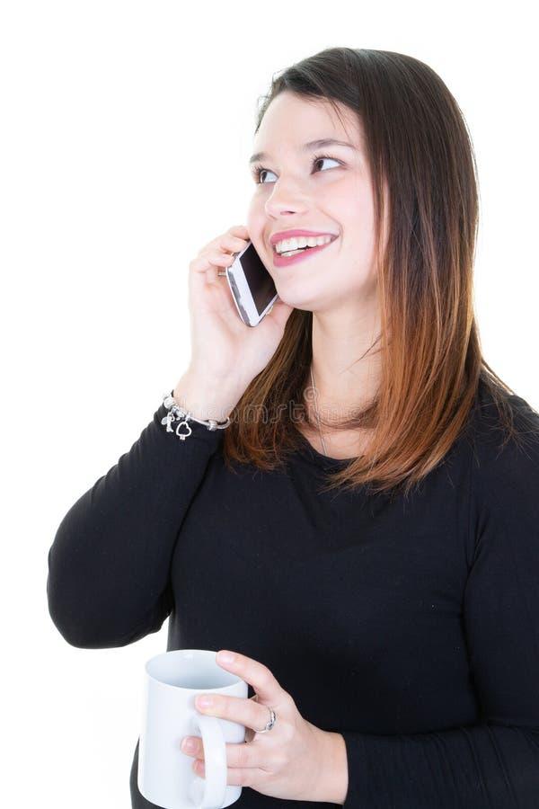 Τσάι κουπών κατανάλωσης γυναικών και χρησιμοποίηση του smartphone στο άσπρο υπόβαθρο στοκ εικόνες