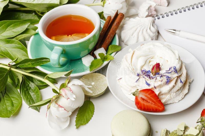 τσάι με τα κέικ, τα φρούτα και τα λουλούδια σε έναν άσπρο πίνακα στοκ φωτογραφίες