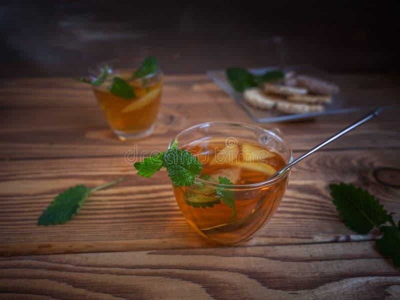 Τσάι με τα μήλα στις κούπες γυαλιού, ένα κουταλάκι του γλυκού στα τσιπ ενός θερμού ξύλινου υποβάθρου, φρούτων και δημητριακών στοκ εικόνες