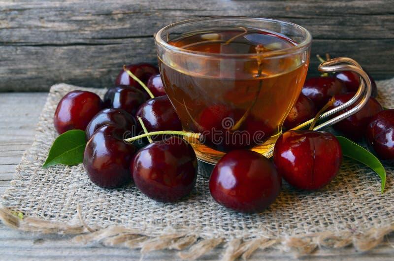 Τσάι με τα πρόσφατα επιλεγμένα κεράσια σε ένα διαφανές φλυτζάνι γυαλιού σε ένα burlap ύφασμα Τσάι πάγου κερασιών φρούτων στον παλ στοκ εικόνες