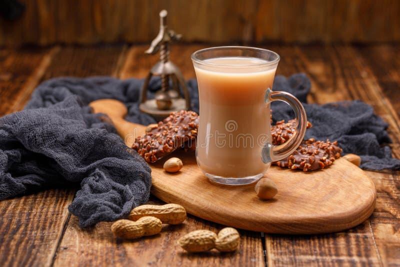 Τσάι με το γάλα και μπισκότα στο φλυτζάνι γυαλιού σε έναν όμορφο πίνακα Ακόμα ζωή με το τσάι, τα μπισκότα, τα καρύδια και ένα παλ στοκ εικόνες με δικαίωμα ελεύθερης χρήσης