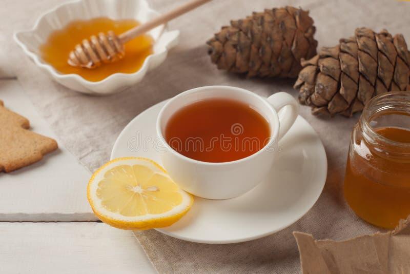 Τσάι με το λεμόνι και το μέλι, τα σπιτικούς μπισκότα και τους κώνους Γλυκό κόμμα τσαγιού το πρωί φθινοπώρου ή χειμώνα στοκ φωτογραφία με δικαίωμα ελεύθερης χρήσης