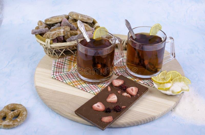 Τσάι, μπισκότα και σοκολάτα σε έναν ξύλινο δίσκο στοκ εικόνες