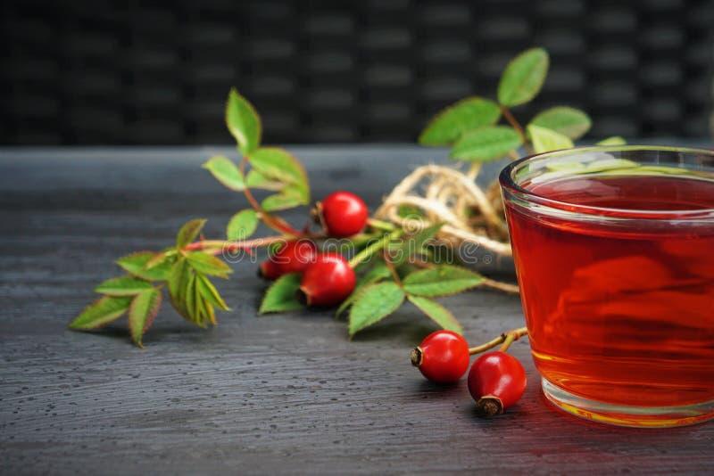 Τσάι ροδαλών ισχίων με το οργανικό μούρο στο μαύρο υπόβαθρο στοκ φωτογραφίες