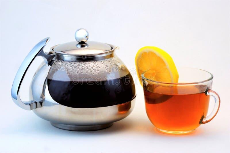 Τσάι σε ένα φλυτζάνι και teapot με το λεμόνι Το χρήσιμο τσάι είναι δημοφιλές αναζωογονώντας ποτό που λαμβάνεται με να βράσει και  στοκ εικόνα