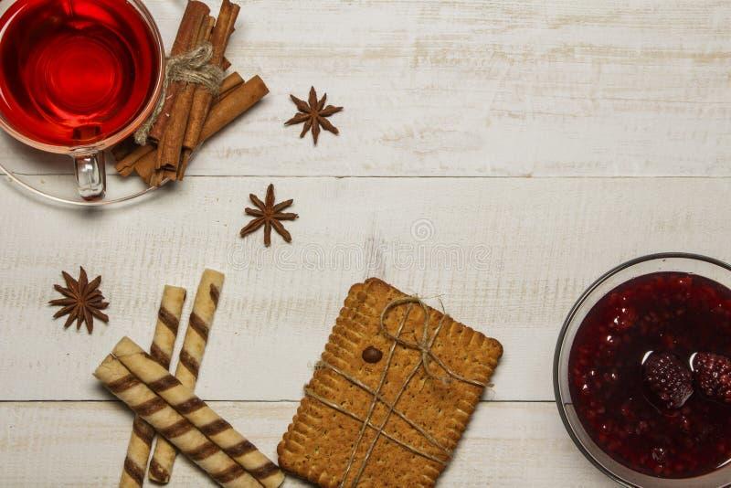 Τσάι σε ένα φλυτζάνι με τη μαρμελάδα σμέουρων, μπισκότα, croissants, κανέλα, γλυκάνισο, ραβδιά καραμέλας Σε έναν άσπρο ξύλινο πίν στοκ φωτογραφία με δικαίωμα ελεύθερης χρήσης