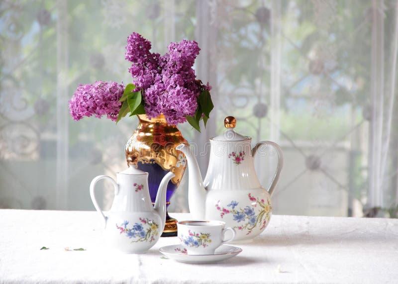 Download Τσάι σε ένα φλυτζάνι, και μια ιώδης ανθοδέσμη σε έναν πίνακα Στοκ Εικόνες - εικόνα από νόστιμος, ύφασμα: 62722436
