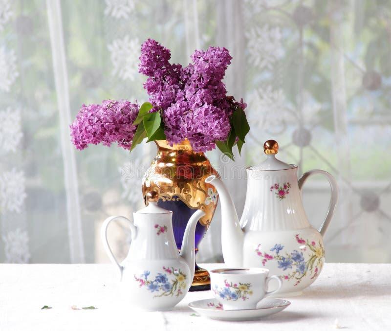 Download Τσάι σε ένα φλυτζάνι, και μια ιώδης ανθοδέσμη σε έναν πίνακα Στοκ Εικόνα - εικόνα από φλυτζάνι, πασχαλιά: 62723189