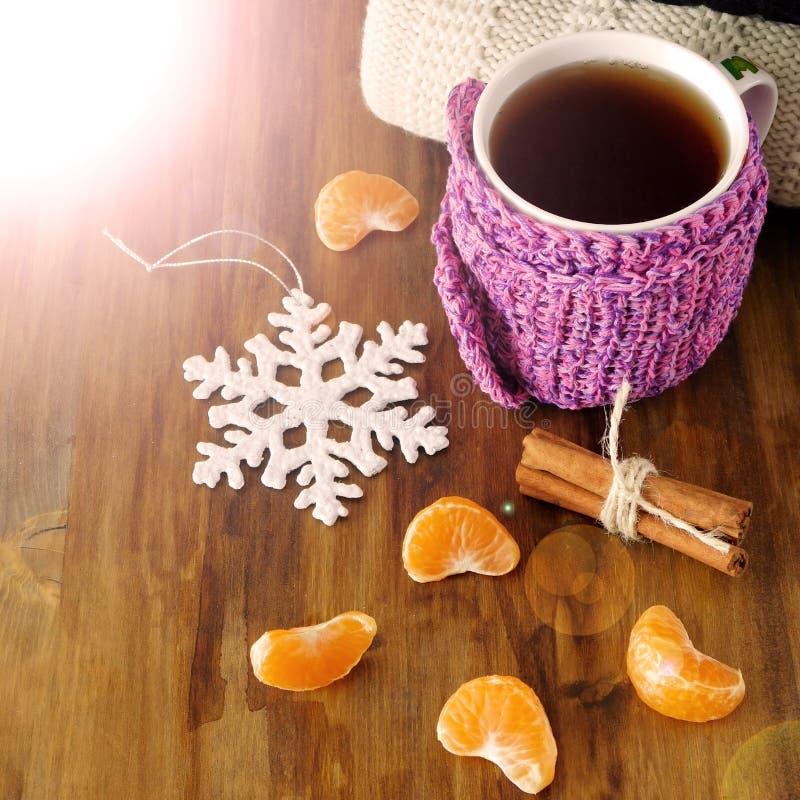 Τσάι σε μια κούπα που τυλίγεται στο μικροσκοπικό μαντίλι που περιβάλλεται από τα τμήματα μανταρινιών στοκ φωτογραφία