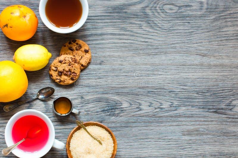Τσάι φρούτων με το λεμόνι, γάλα, μέλι, πορτοκάλι, ρόδι, σε ένα woode στοκ φωτογραφία