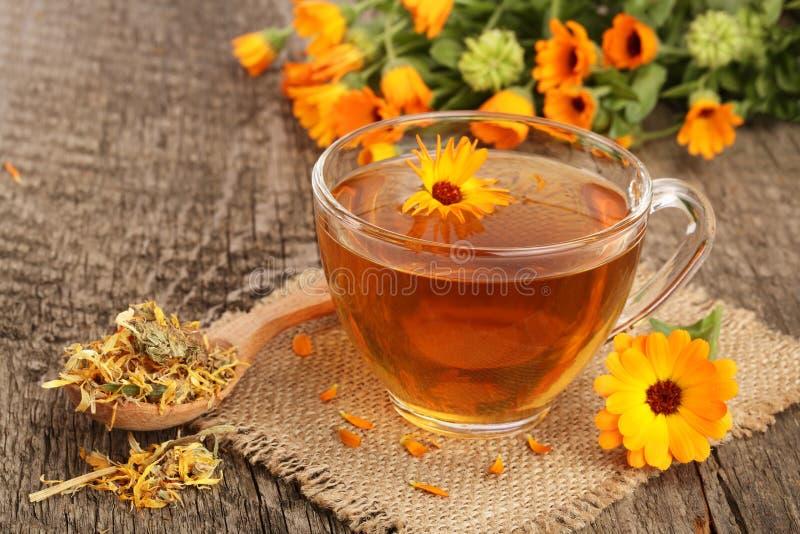 Τσάι Calendula με τα φρέσκα και ξηρά λουλούδια στο παλαιό ξύλινο υπόβαθρο στοκ φωτογραφίες