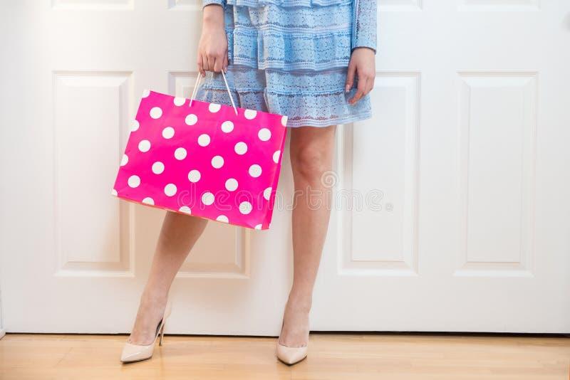 Τσάντα αγορών εκμετάλλευσης γυναικών μετά από το χρόνο αγορών που φορά τα υψηλά τακούνια που στέκονται στο σπίτι κοντά στο ντουλά στοκ φωτογραφία με δικαίωμα ελεύθερης χρήσης