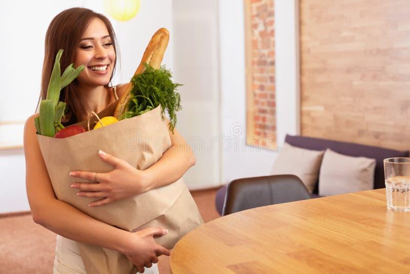 Τσάντα αγορών εκμετάλλευσης γυναικών με τα λαχανικά που στέκονται στο Kitch στοκ φωτογραφίες