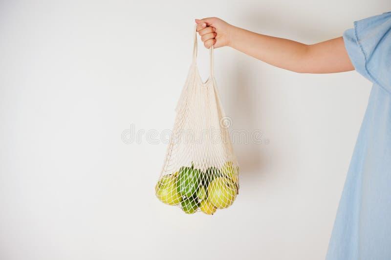 Τσάντα αγορών πλέγματος eco εκμετάλλευσης κοριτσιών με τα πράσινα και κίτρινα φρούτα στο ελαφρύ υπόβαθρο στοκ φωτογραφία με δικαίωμα ελεύθερης χρήσης