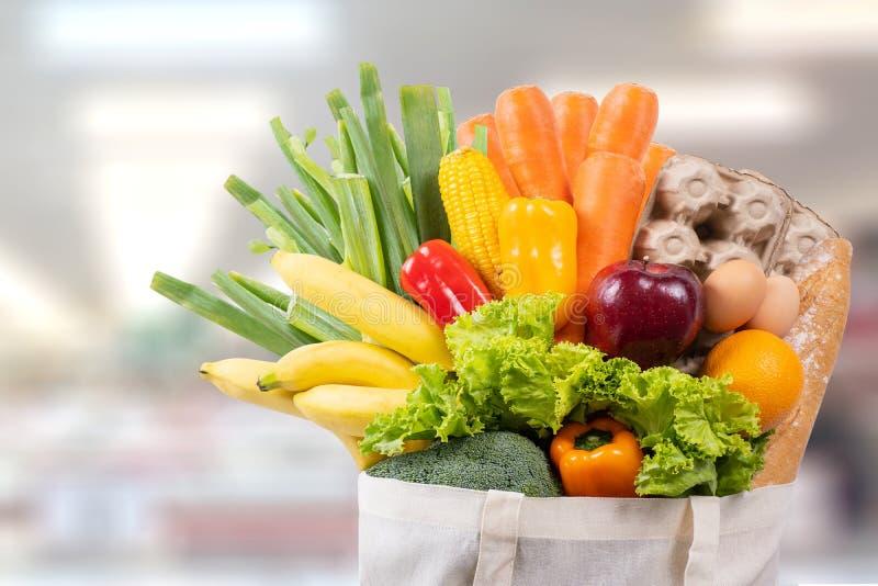 Τσάντα αγορών χρήσης ημέρας Eco με το παντοπωλείο λαχανικών που ψωνίζει στη γουλιά στοκ φωτογραφίες