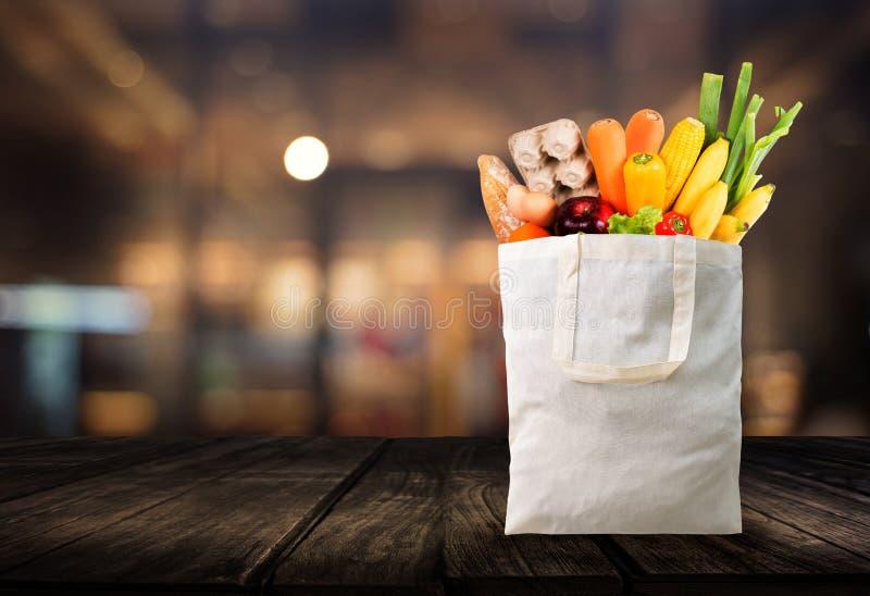 Τσάντα αγορών χρήσης ημέρας Eco με το παντοπωλείο λαχανικών που ψωνίζει στη γουλιά στοκ φωτογραφία με δικαίωμα ελεύθερης χρήσης