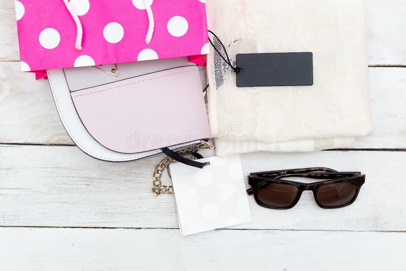 Τσάντα γυναικών ` s και μια μπλούζα με τις ετικέτες σε ένα ξύλινο υπόβαθρο στοκ φωτογραφία με δικαίωμα ελεύθερης χρήσης