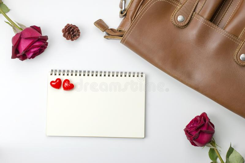 Τσάντα δέρματος με τα τριαντάφυλλα και κενό σημειωματάριο στο άσπρο υπόβαθρο Τ στοκ εικόνα