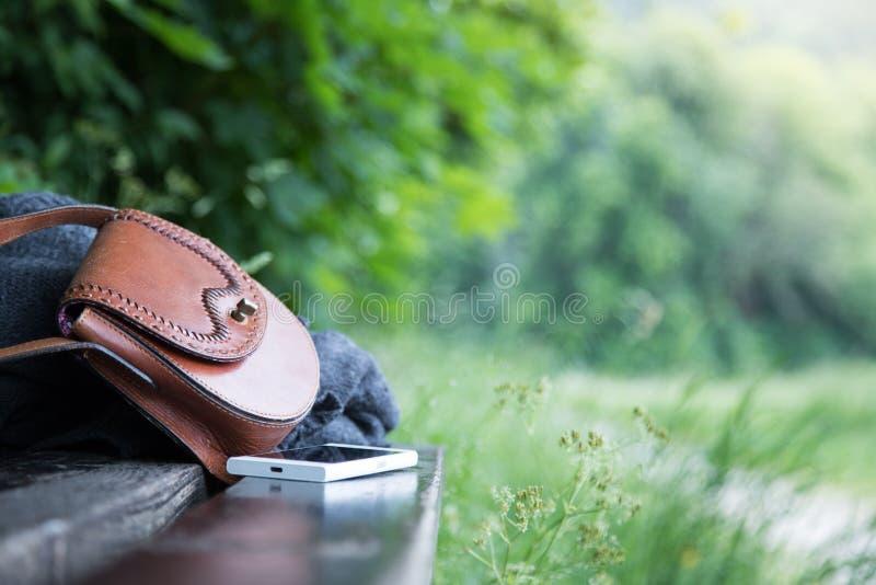 Τσάντα δέρματος, smartphone και σακάκι σε έναν πάγκο πάρκων, κανένας στοκ φωτογραφία με δικαίωμα ελεύθερης χρήσης