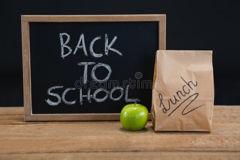 Τσάντα εγγράφου μεσημεριανού γεύματος, πράσινες μήλο και πλάκα με το κείμενο πίσω στο σχολείο στον ξύλινο πίνακα στοκ εικόνα