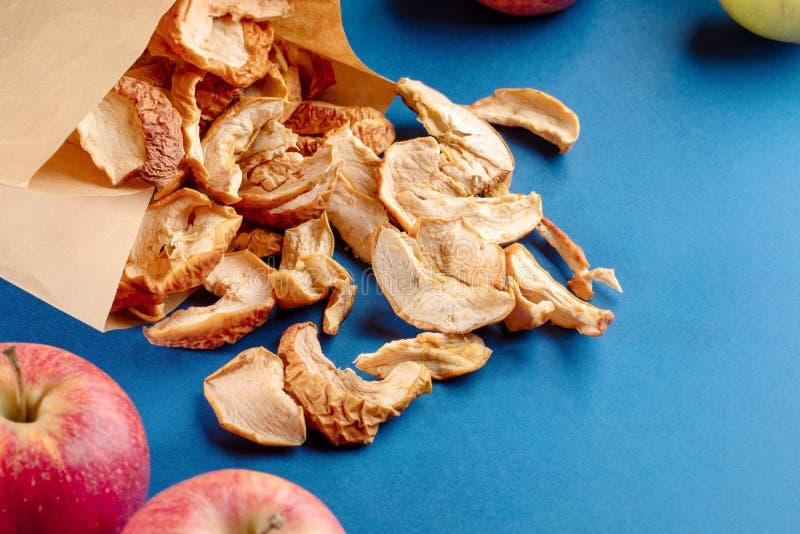 Τσάντα εγγράφου με τις διασκορπισμένες ξηρές φέτες μήλων και ολόκληρα τα φρούτα στο μπλε υπόβαθρο στοκ εικόνες