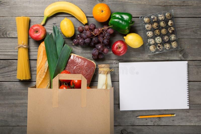 Τσάντα εγγράφου των τροφίμων και του σημειωματάριου με την κενή σελίδα στοκ φωτογραφία με δικαίωμα ελεύθερης χρήσης