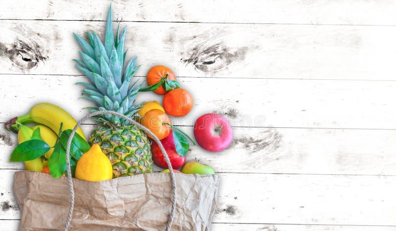 Τσάντα καφετιού εγγράφου που γεμίζουν με τα φρέσκα υγιή οργανικά φρούτα στο άσπρο ξύλινο επιτραπέζιο κλίμα στοκ φωτογραφίες με δικαίωμα ελεύθερης χρήσης